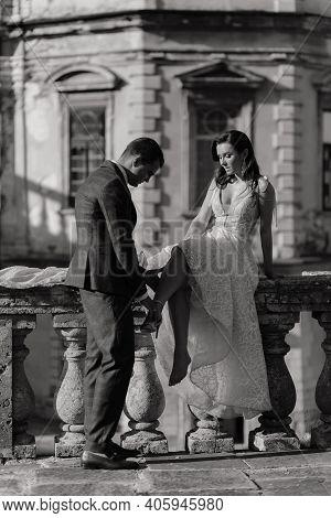 Groom Helping Bride To Take Off Wedding Shoes Stylish Newlywed Wedding Couple