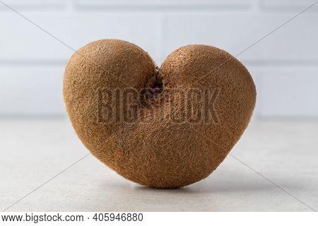 Ugly Heart Shaped Kiwi Fruit On Grey Table. Organic Deformed Produce. Trendy Strange Food. Odd Missh