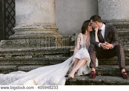 Happy Bride And Groom Sitting On The Stairs Of The Old Palace In Front Of The Columns. Wedding Coupl