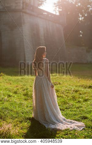 Beautiful Bride In The Luxurious Wedding Dress Looking To The Side In Front Of Old Wall At The Sunse