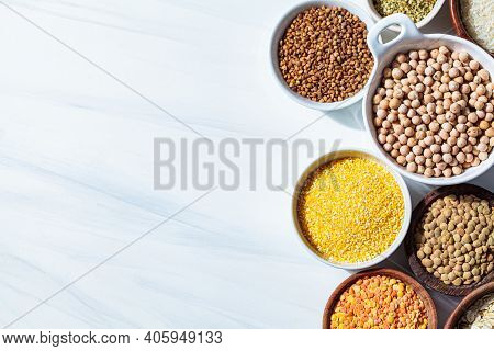 Assorted Dry Cereals And Legumes In White And Wooden Bowls, White Background. Vegan Protein Concept.