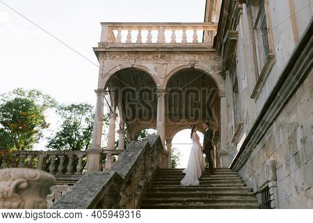 Newlywed Standing On The Stairs Of The Old Palace And Holding Each Other Hands