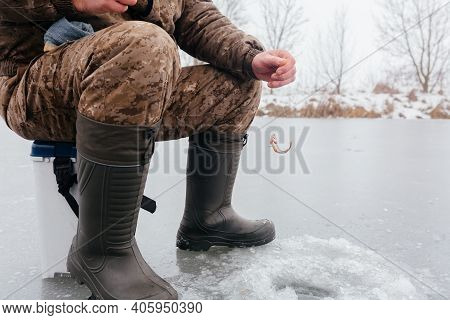 Faceless Man Pulling Fish From The Ice Hole While Ice Fishing. Pulling Caught Fish From A Hole In Th