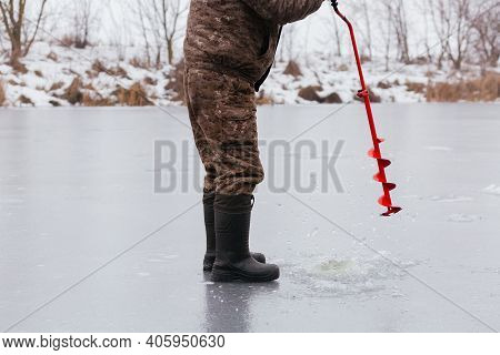 Faceless Fisherman Making The Hole In Snowy Ice At Lake By Red Ice Screw. Winter Fishing Concept. Ic