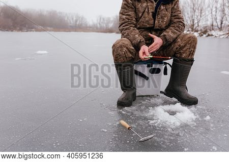 Fisherman Catching Fish In The Ice Hole On The Frozen Lake. Faceless Man Fishing In Winter. Winter F