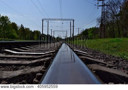 The Railway Goes Into The Distance, The Rails Are Sleepers. Spring Or Summer Sunny Day. Travel Conce