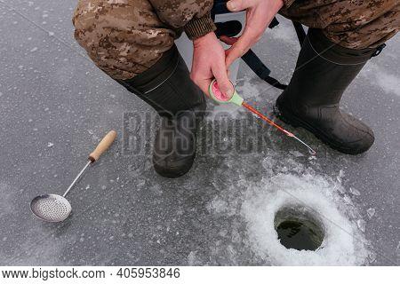 Faceless Fisherman Jiggling Bait In An Ice Hole. Winter Fishing On Ice. Ice Fishing. Man Catching Fi