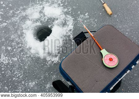 Close Up Ice Fishing Tackle And Equipment Near The Ice Hole. Winter Fishing Concept. Ice Fishing