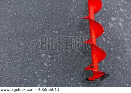 Ice Screw On The Frozen Lake With Place For Your Text. Ice Fishing. Winter Fishing Concept. Ice Back