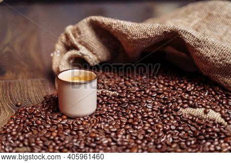 A Coffee Bag And Coffee Beans Lying On A Wooden Floor. There Is Brown Cup With Espresso.