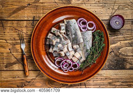 Pickled Marinated Herring Fish Sliced Fillet On A Plate With Thyme And Onion. Wooden Background. Top