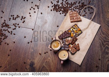 Two Cups Of Espresso Coffee With Grains, Craft Bag And Chocolate On A Wooden Table On A Dark Backgro