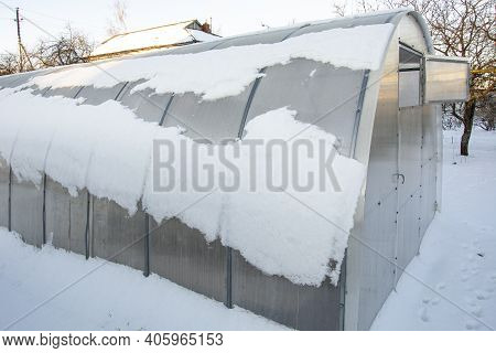 Greenhouses Under The Snow. Snow On The Roof Of The Greenhouse. A Polycarbonate Greenhouse For Plant