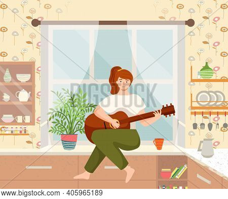 Woman Is Playing The Guitar Sitting On The Kitchen Table. Musician Composes Songs And Sings At Home.