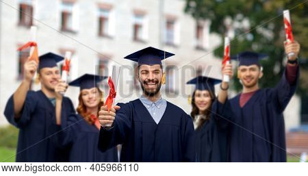 education, graduation and school concept - happy smiling male graduate student in mortar board and bachelor gown with diploma over group of people on campus background