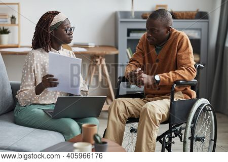 Portrait Of African-american Couple With Handicapped Man Using Wheelchair Working From Home Together