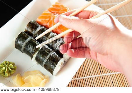 Close Up Of Chopsticks Taking Portion Of Sushi Roll On The Table Restaurant Eating Sushi Roll Using