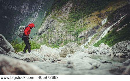 Caucasian Hiker Wearing Red Raincoat On The Scenic Alpine Trailhead. Walking Between Dramatic Alpine