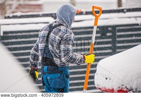 Caucasian Men In His 40s Removing Snow During Heavy Snow Fall Using Large Snow Shovel.