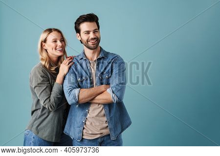 Young happy couple hugging and smiling while looking aside isolated over blue background