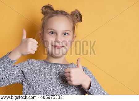 Portrait Of Cute Little Girl Smiling Toothless And Showing Thumbs Up On Yellow Background. Close-up