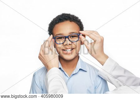 Ophthalmologist Tries On Eyeglasses To African American Little Boy, Close-up. Treatment Of Childrens