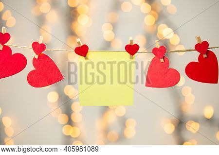 Blank Yellow Sticky Note Hanging With Red Hearts With Bokeh Background, Romantic Valentines Day Conc