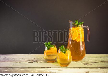 Cold Summer Orange Lemonade In Pitcher And  Glasses On Wooden Table On Dark Background. View With Co