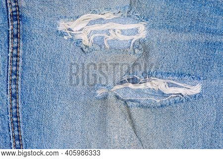 Rubbed Places And Holes On Blue Jeans. Texture Of The Old Torn Denim Showing The Frayed Threads, Fra