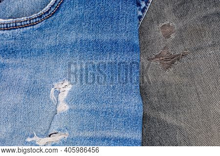 Hole And Worn Places In An Old Torn Blue And Black Jeans Showing The Frayed Threads And Fabric Textu