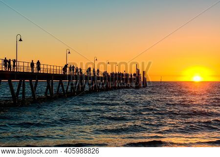 Glenelg Beach Jetty With People Walking Along At Sunset During Summer Evening