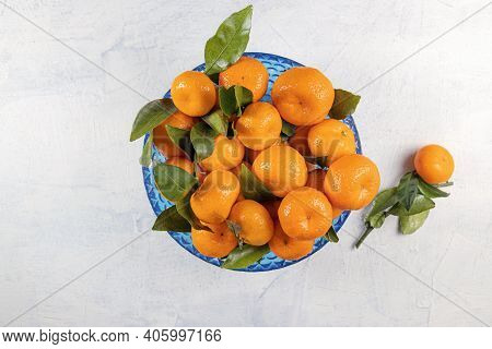Orange Tangerines With Green Leaves In Blue Plate On A White Stone Background. Ripe, Fresh, Tasty An