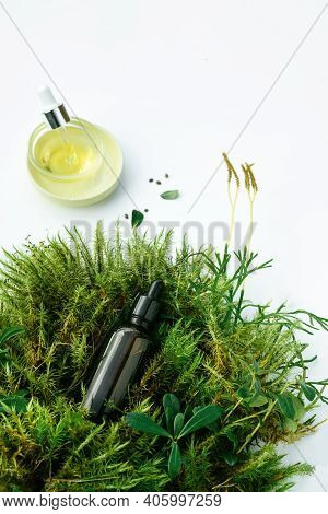 Bottles With Natural Cosmetic Serum Oils For Face And Body Care With Fresh Plants On White Backgroun