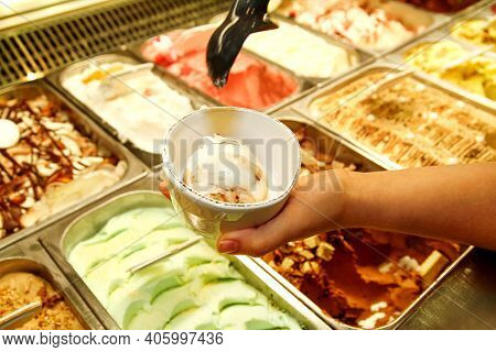 Female Hand With Scoop Takes Ice Cream From The Fridge And Serving In Ceramic White Cups. Woman Taki