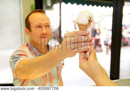 Handsome Happy Man Sells Ice Cream In Shop. Kind Female Seller In Candy Store Gives Ice Cream To Boy