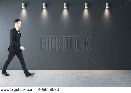 Businessman Walking In Gallery Interior With Lamps And Blank Gray Wall. Gallery And Art Concept. Moc