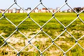 Chain link fence against a green grass and houses in the background poster