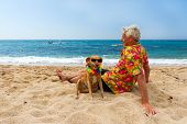 Relaxing elderly man with dog laying at the beach poster