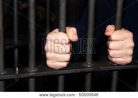 Man behind jail bars reaching out