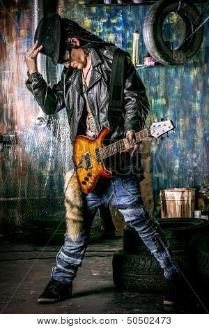 Heavy metal musician is playing electrical guitar in the old garage.