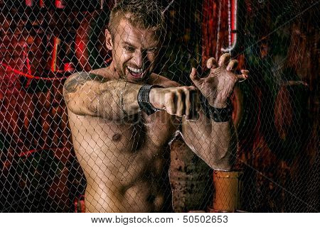 Handsome muscular man breaks through the metal mesh with a fist. Grunge background.