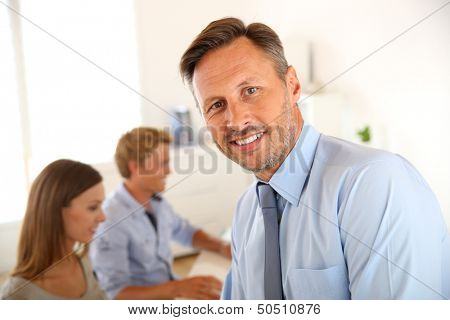 Business manager with employees in background