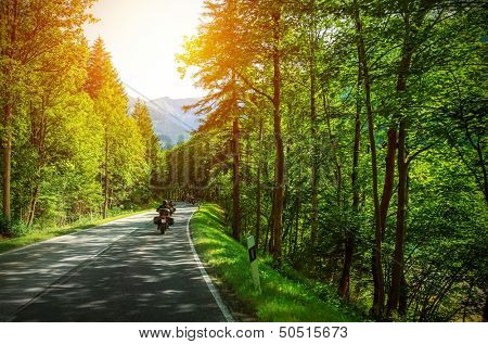 Biker on mountainous road in sunset light, motorcyclist on highway, drive motorbike along Alps, Europe trip, beautiful forest, active lifestyle