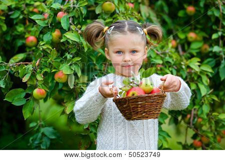 Cute girl in apple orchard