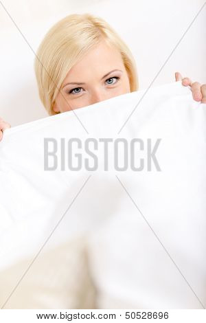 Woman in bed covers her face with white eiderdown