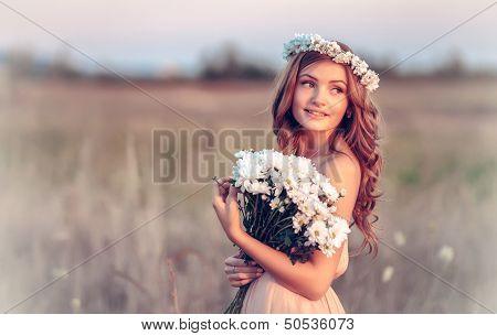 beautiful girl in a camomile wreath