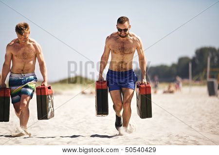 Strong crossfit guys lifting heavy jerrycans outside on beach. Muscular active people in 20s training to maintain healthy lifestyle. poster