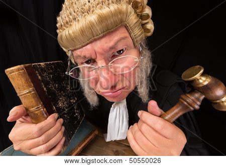 Grumpy old judge in extreme wide angle closeup with hammer and wig