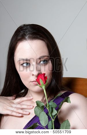 An Attractive Young Woman Smelling A Rose