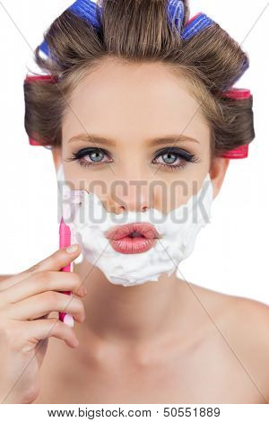 Sexy young model in hair curlers posing with razor looking at camera
